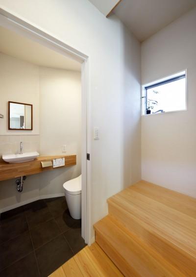 エントランスつながるヒノキの階段と横のお手洗い (中庭のある無垢な珪藻土の家 – 共働き世帯の家事効率を練りに練ったプラン –)