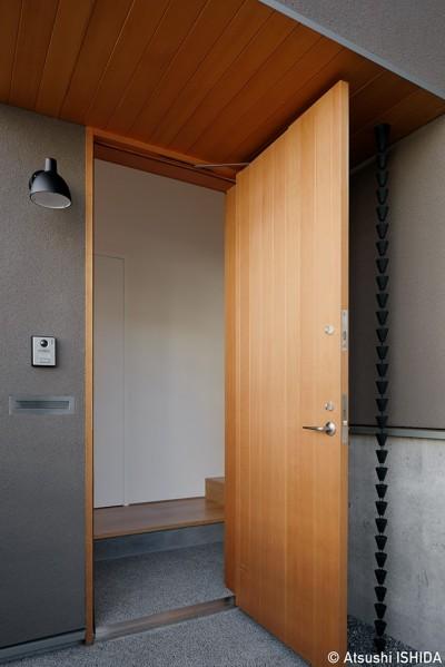 玄関ポーチ (周囲に閉じて内部に開く傾斜地の家)
