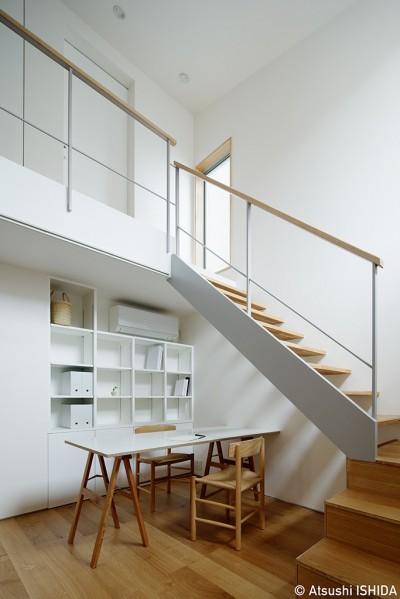 家族の図書スペース (周囲に閉じて内部に開く傾斜地の家)