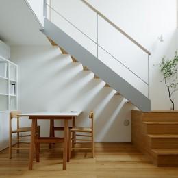 周囲に閉じて内部に開く傾斜地の家 (家族の図書スペース)