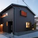 周囲に閉じて内部に開く傾斜地の家の写真 南東外観(夕景)