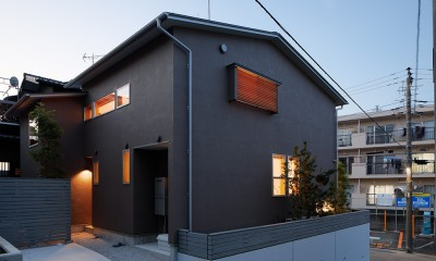 南東外観(夕景)|周囲に閉じて内部に開く傾斜地の家