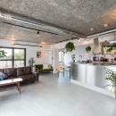 無機質な空間に映えるグリーン。モルタル床の家の写真 リビングダイニング
