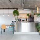 無機質な空間に映えるグリーン。モルタル床の家の写真 キッチン