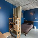 無機質な空間に映えるグリーン。モルタル床の家の写真 ベッドルーム