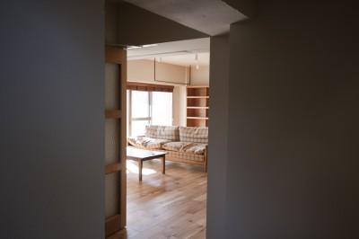 AShouse 所蔵する本の数が多い家族のマンションのリノベーション (玄関からリビングを見る)