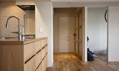 AShouse 所蔵する本の数が多い家族のマンションのリノベーション (リビングから玄関をみる)