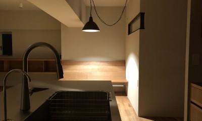 AShouse 所蔵する本の数が多い家族のマンションのリノベーション (夜にキッチンからダイニングをみる)