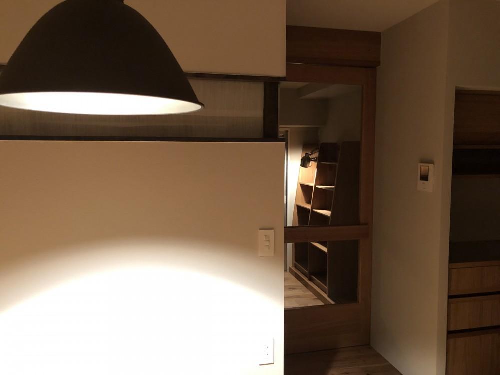 AShouse 所蔵する本の数が多い家族のマンションのリノベーション (窓辺の本棚をガラス越しに見る)
