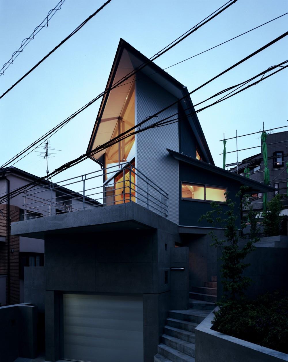 【丘を望む家 】 谷を超えて眺望が広がる急斜面に建つ家 (夕景 道路からの眺め)