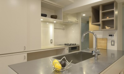 第二の人生を夫婦で楽しむ光と風が通り抜けるマンションのスケルトンリフォーム (家の中心にあるアイランドキッチン)
