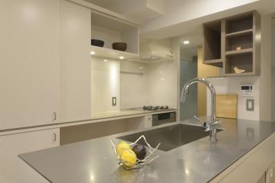 家の中心にあるアイランドキッチン (第二の人生を夫婦で楽しむ光と風が通り抜けるマンションのスケルトンリフォーム)