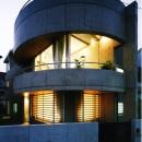 【T字路に建つ家】  外へと膨らみ内を包み込む曲面の壁の写真 外観(夕景)
