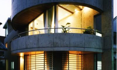 【T字路に建つ家】  外へと膨らみ内を包み込む曲面の壁 (外観(夕景))