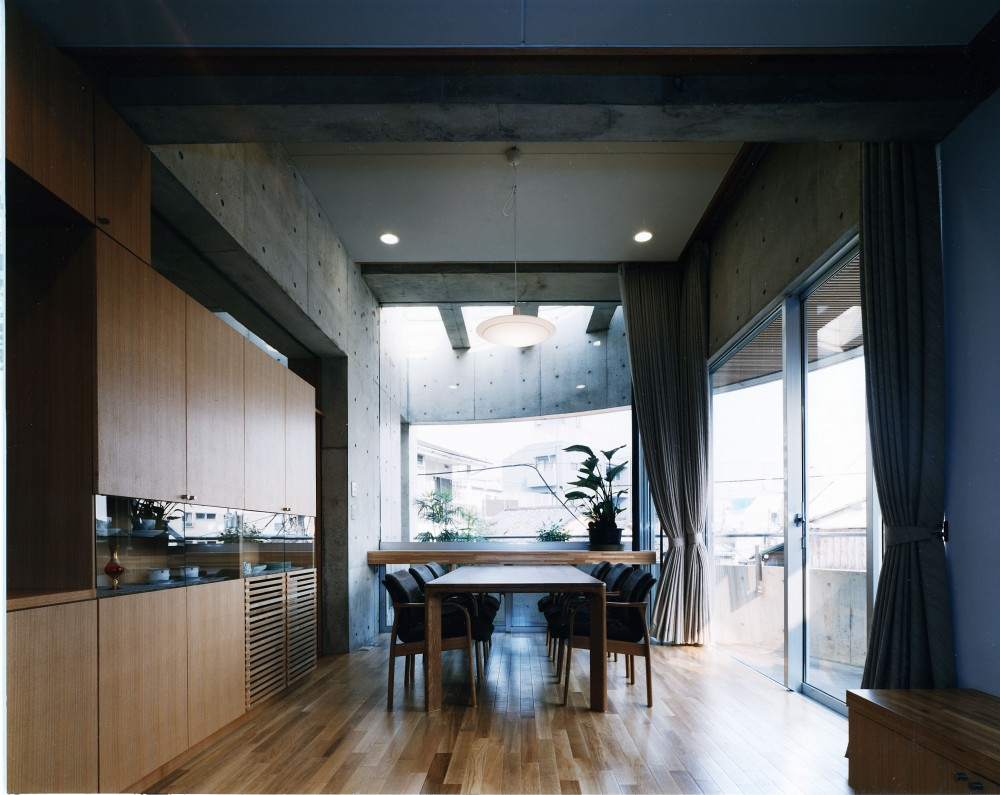【T字路に建つ家】  外へと膨らみ内を包み込む曲面の壁 (リビングダイニング)