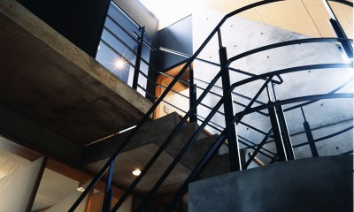 【T字路に建つ家】  外へと膨らみ内を包み込む曲面の壁 (階段)