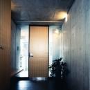【T字路に建つ家】  外へと膨らみ内を包み込む曲面の壁の写真 玄関
