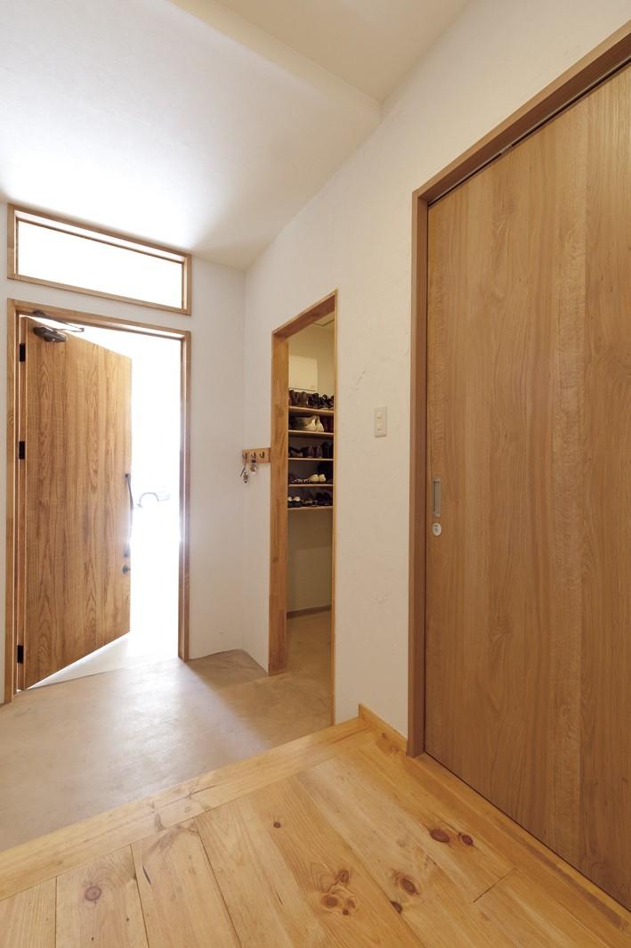 大阪府Sさん邸:中古リノベーションで開放感のある個性的な空間に (ガレージから続く広々玄関)