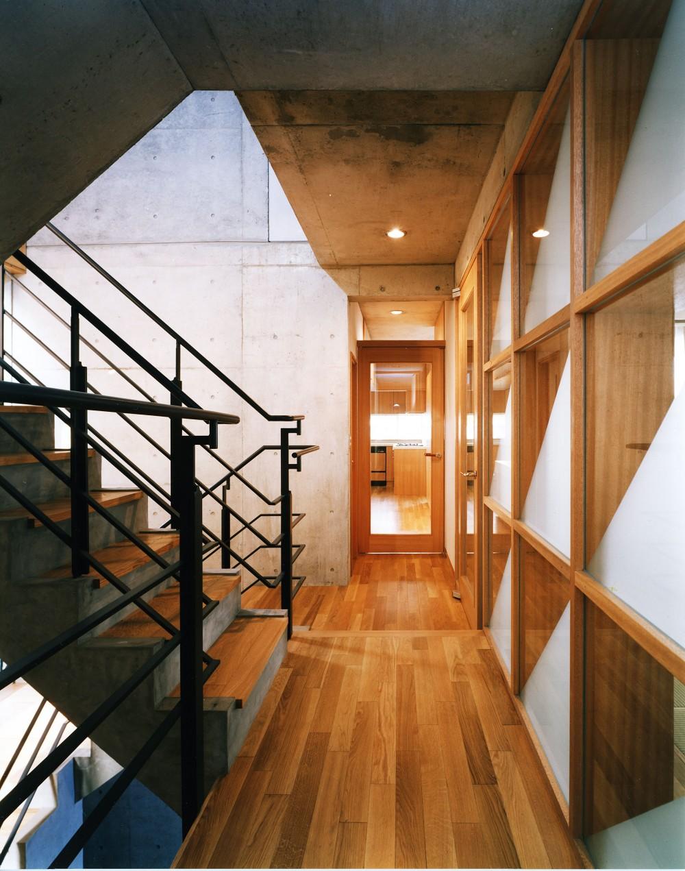 【T字路に建つ家】  外へと膨らみ、内を包み込む曲面の壁 (階段ホール)