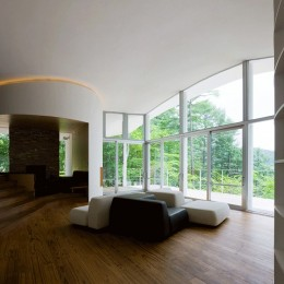 軽井沢カウンターポイント - 森に浮かぶコンクリート屋根の別荘 - (曲面壁の間からリビングへ向かう)