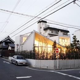 ねじれ屋根の家 - 弧を描く勾配天井 - (夕景)