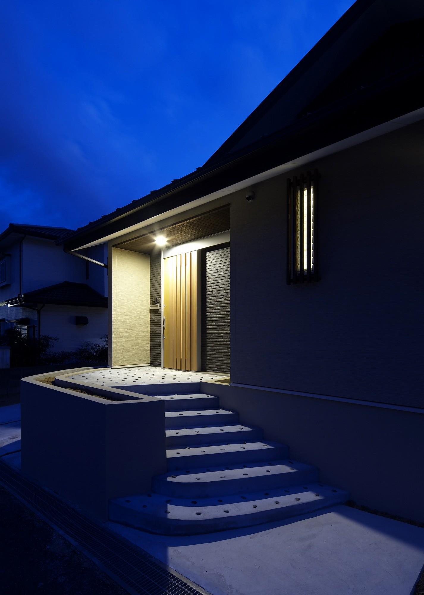 外観事例:玄関の夕景(「ひかりヶ丘の家」~借景を楽しむ和モダンなスキップフロアーの家)