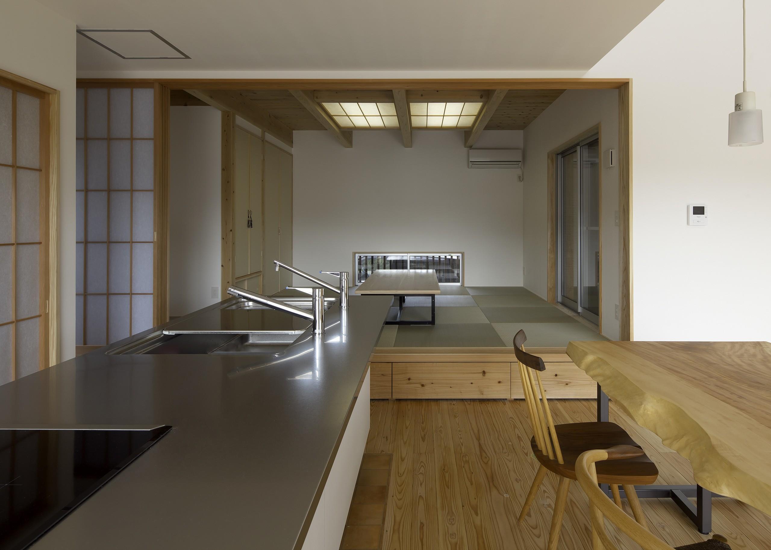 キッチン事例:DKから小上りの和室を見る。小上り部分には引出を設けて収納に、引出しの面板は一枚板を加工して造りました。木目が通って綺麗です。(「ひかりヶ丘の家」~借景を楽しむ和モダンなスキップフロアーの家)