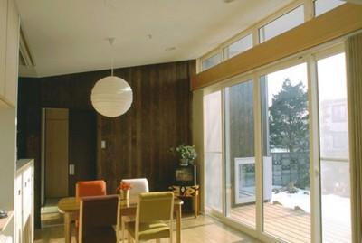テラス越しに庭へとつながるダイニング (3断面の家 - 寒冷地のコンパクト住居)