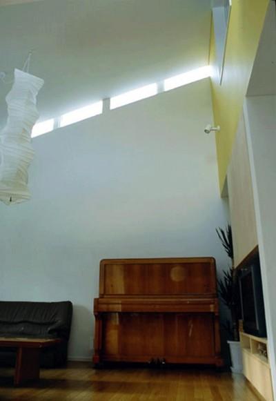 ハイサイドライトのある吹抜リビング (3断面の家 - 寒冷地のコンパクト住居)