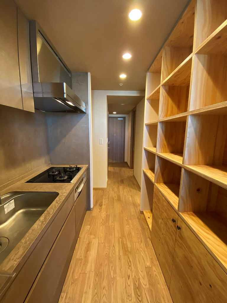 無垢の床とモールテックス仕上げの部屋 (キッチンと収納棚)