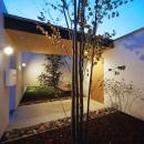 【ikenouchi】塀をくぐると広がる開放感。移り変わる光、美しい景色や木肌が美しい平屋の写真 玄関アプローチの夕景