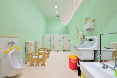 明るいグリーンの壁が特徴のトイレ (横須賀市 ~にじのそら保育園~)