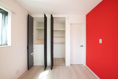 大きなクローゼットとアクセントカラーの赤が映える寝室 (収納の工夫で広く見せる狭小住宅~父の残した小さなお城)