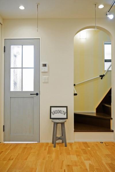 縦ストライプの壁とアーチで上への広がりを感じさせる階段スペース (収納の工夫で広く見せる狭小住宅~父の残した小さなお城)
