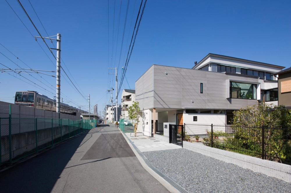 鶴見の家/線路沿いの細長い敷地に建つ木造3階建ての2世帯住宅 (外観/目の前を電車が通る様子)