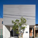 鶴見の家/線路沿いの細長い敷地に建つ木造3階建ての2世帯住宅の写真 外観/無機質な素材を組み合わせています