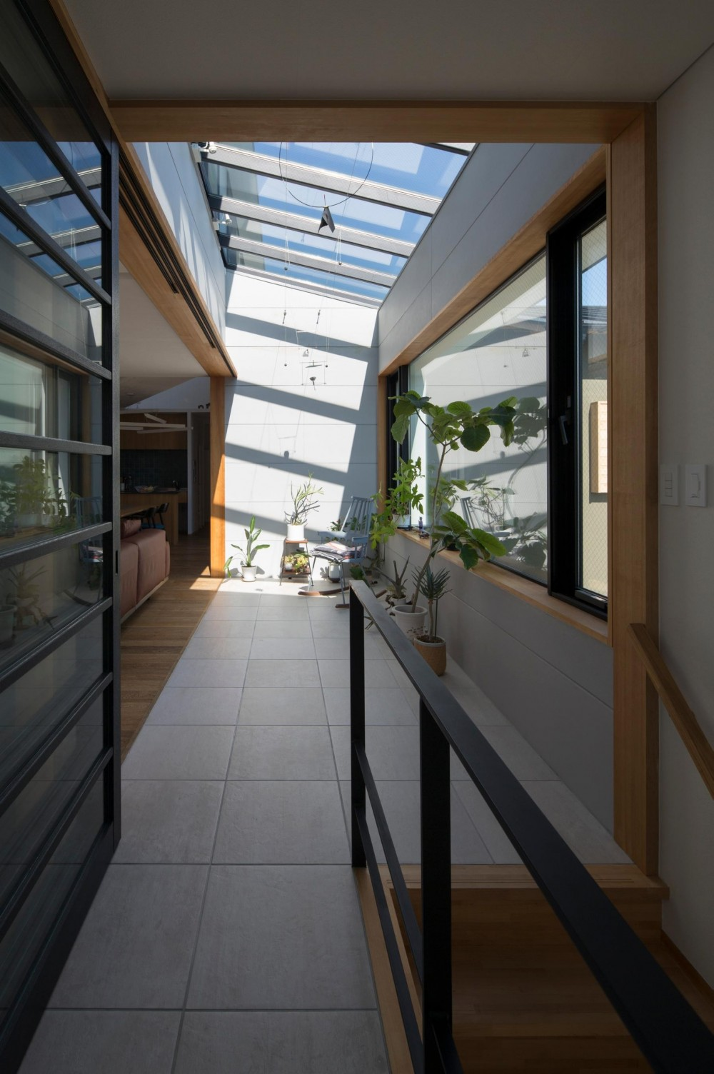 鶴見の家/線路沿いの細長い敷地に建つ木造3階建ての2世帯住宅 (アトリウム/2階の玄関ホールを兼ねたアトリウム)