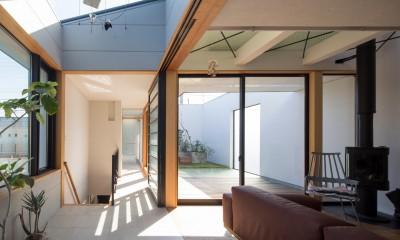 鶴見の家/線路沿いの細長い敷地に建つ木造3階建ての2世帯住宅 (アトリウム・リビング/2階リビングの奥にテラス。)
