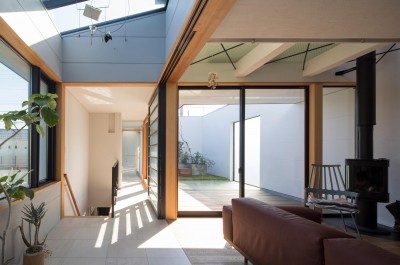 アトリウム・リビング/2階リビングの奥にテラス。 (鶴見の家/線路沿いの細長い敷地に建つ木造3階建ての2世帯住宅)