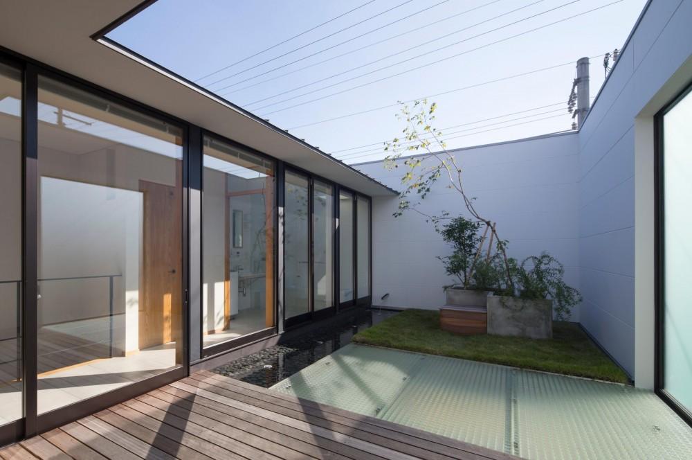 鶴見の家/線路沿いの細長い敷地に建つ木造3階建ての2世帯住宅 (テラス/左手に開放的な水回りが並びます。敷地の前を走る線路からの視線を遮るため、防音壁を兼ねた壁でテラスを囲んでいます。)