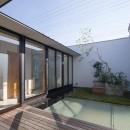 鶴見の家/線路沿いの細長い敷地に建つ木造3階建ての2世帯住宅の写真 テラス/左手に開放的な水回りが並びます。敷地の前を走る線路からの視線を遮るため、防音壁を兼ねた壁でテラスを囲んでいます。