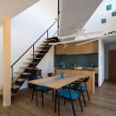 鶴見の家/線路沿いの細長い敷地に建つ木造3階建ての2世帯住宅の写真 2階ダイニング・キッチン/吹き抜けを斜めに横切る渡り廊下。階段やキッチンのデザインに合わせてダイニングテーブルもデザインしています。