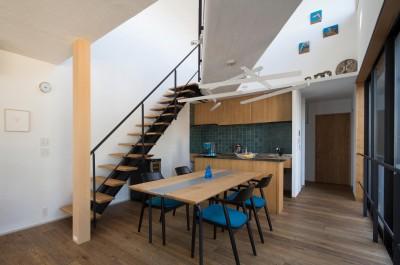鶴見の家/線路沿いの細長い敷地に建つ木造3階建ての2世帯住宅 (2階ダイニング・キッチン/吹き抜けを斜めに横切る渡り廊下。階段やキッチンのデザインに合わせてダイニングテーブルもデザインしています。)