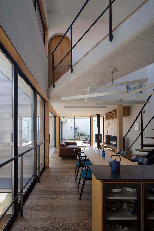 鶴見の家/線路沿いの細長い敷地に建つ木造3階建ての2世帯住宅 (2階ダイニング・リビング/ダイニングからリビング、テラスを見る。渡り廊下の突き当りは子ども部屋になっています。)