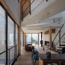 鶴見の家/線路沿いの細長い敷地に建つ木造3階建ての2世帯住宅の写真 2階ダイニング・リビング/ダイニングからリビング、テラスを見る。渡り廊下の突き当りは子ども部屋になっています。