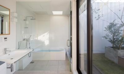 鶴見の家/線路沿いの細長い敷地に建つ木造3階建ての2世帯住宅 (洗面所、浴室/プライバシーが守られたテラスに面する開放的な水回り。)