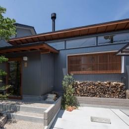 伊勢田の家/夫婦2人のためのコンパクトな平屋の住まい (外観/薪ストーブ用の薪が積み上げられています。)