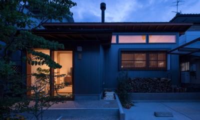 伊勢田の家/夫婦2人のためのコンパクトな平屋の住まい (外観の夕景/LDKの高窓と格子からも暖かい光が漏れています。)