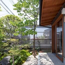 玄関ポーチ/玄関のガラス戸の前に設えられた小さな前庭が訪れる人を出迎えます (伊勢田の家/夫婦2人のためのコンパクトな平屋の住まい)