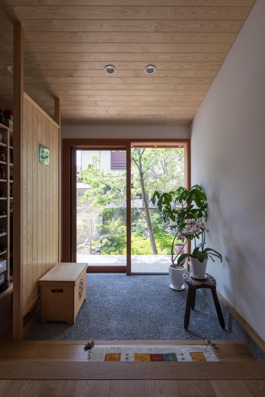 伊勢田の家/夫婦2人のためのコンパクトな平屋の住まい (玄関/ガラス戸の向こうに前庭の緑が見えています。左側には衝立で仕切られたシューズクローク。)